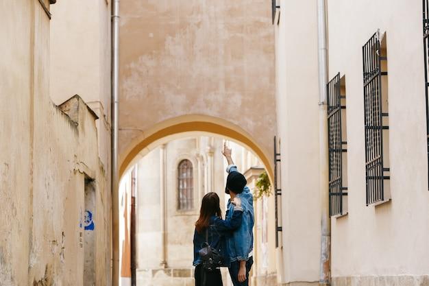 Schauen sie von hinten auf das paar touristen, die etwas beobachten, während sie durch die stadt laufen