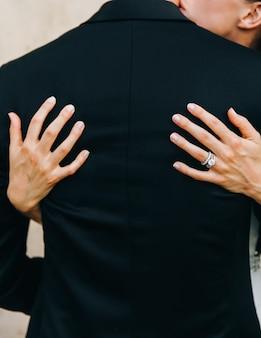 Schauen sie von hinten auf die braut, die bräutigamangebot umarmt. hände auf seinem rücken