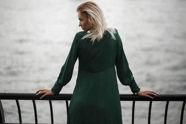 Schauen sie von hinten auf träumerische frau im grünen kleid, das vor dem fluss in new york steht