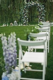 Schauen sie von hinten auf weiße stühle, die auf dem grünen rasen vor dem hochzeitsaltar stehen