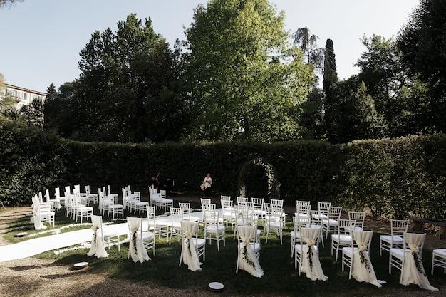 Schauen sie von hinten auf weiße stühle, die für hochzeitszeremonie angeordnet sind