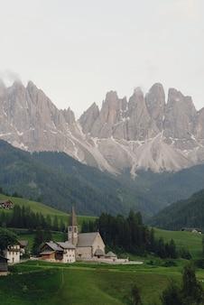 Schauen sie von weitem auf eine kirche in den italienischen dolomiten