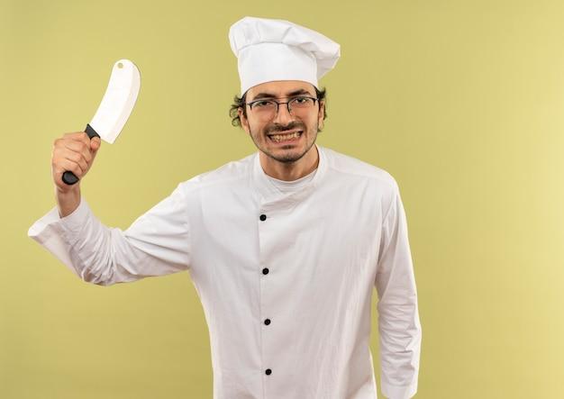 Schauen zufriedener junger männlicher koch mit kochuniform und gläsern, die hackmesser auf grünem hintergrund anheben