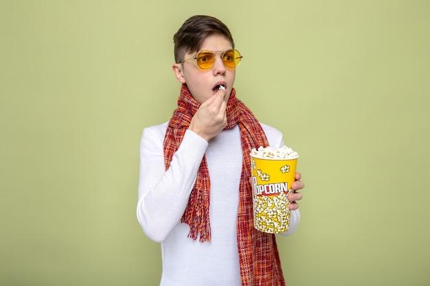 Schauender junger gutaussehender kerl mit schal mit brille, der popcorn-eimer hält