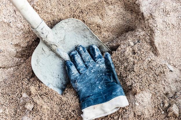 Schaufel mit beton verschmiert in einem sandhaufen für die herstellung von beton und einem arbeiterhandschuh.