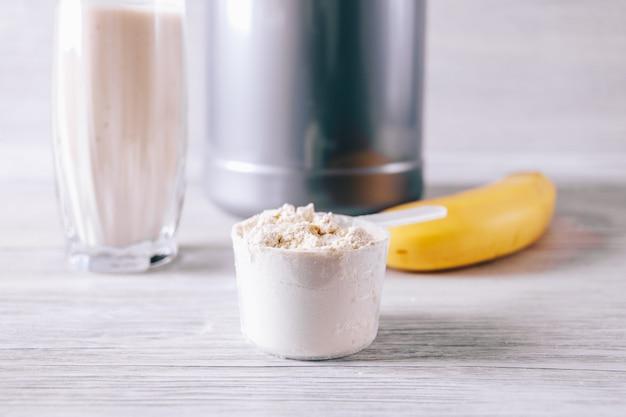 Schaufel mit proteinpulver, banane und glas