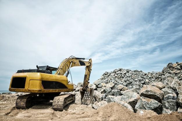 Schaufelmaschinenarbeiten mit sand und steinen