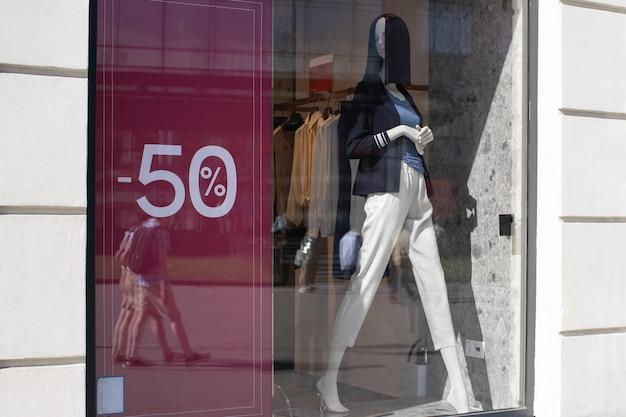 Schaufenster des bekleidungsgeschäfts in der saison der rabatte, schaufensterpuppe in moderner bequemer damenbekleidung, zeichen des rabattes 50 prozent. concept shopping, schwarzer freitag, verkauf. horizontal