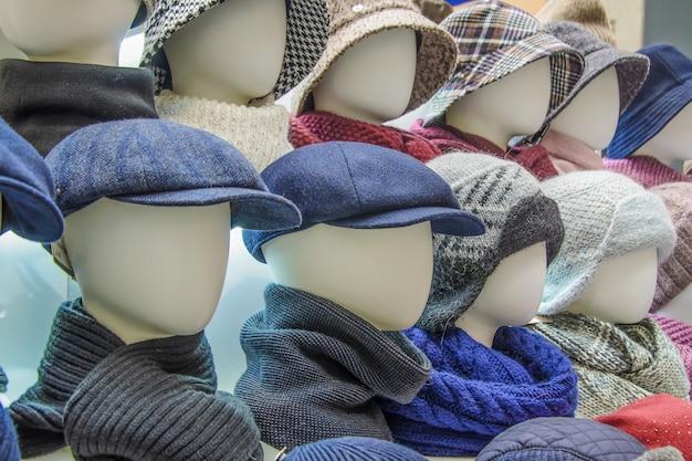 Schaufenster mit verschiedenen kopfbedeckungen für männer und frauen für die herbst- und wintersaison