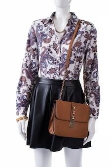 Schaufensterpuppe mit tasche und rock. braune damenhandtasche und armband. zarter schmuck mit brauner tasche. modische kleidung für den frühling.