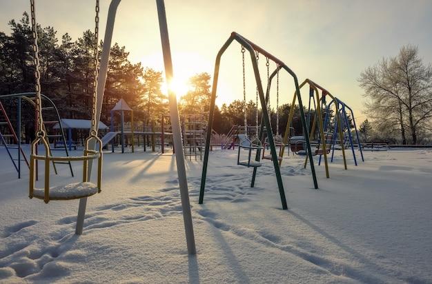 Schaukeln auf dem schneebedeckten spielplatz im winter. bäume mit raureif bedeckt.