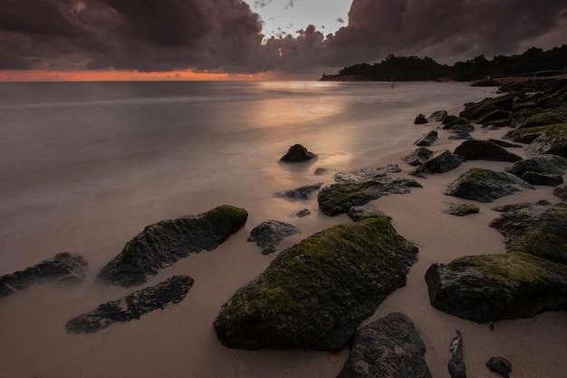 Schaukeln sie auf dunklen strand mit damatic wolke am morgen mit sonnenaufgang