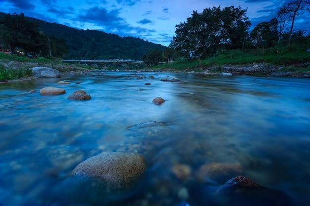 Schaukeln sie in fluss und schönen sonnenuntergang in kiriwong-dorf