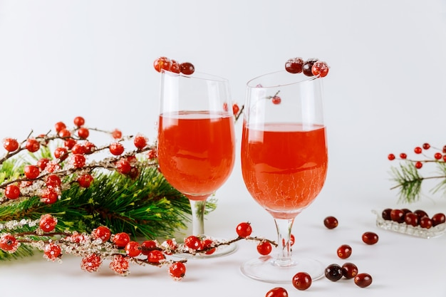 Schaumgetränk aus preiselbeeren in glas mit roter beerendekoration auf weißer oberfläche.