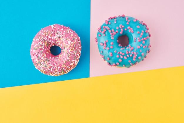 Schaumgummiringe auf pastellrosa-, gelber und blaueroberfläche. kreative lebensmittelzusammensetzung des minimalismus. flacher laienstil