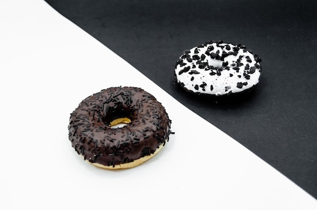 Schaumgummiringe mit der schokolade, die mit glasiert wird, besprüht die schaumgummiringe, die auf weißem schwarzem abstraktem hintergrund lokalisiert werden