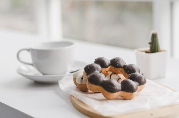 Schaumgummiringe und tasse kaffee auf einer weißen hölzernen tabelle