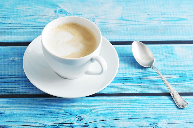 Schaumiger kaffee mit cappuccino in einem weißen becher auf einem blauen hintergrund