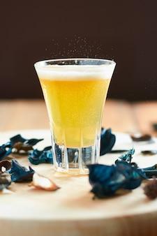 Schaumiges gelbes getränk im glas auf holztisch mit geringer schärfentiefe
