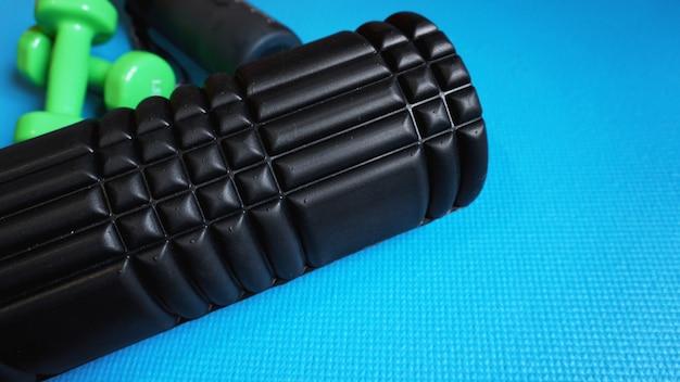 Schaumstoffroller mit grünen hanteln gym fitnessgeräte blauer hintergrund selbst myofascial release - mfr.