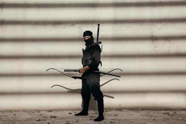 Schauspieler, der bogenschützenrolle in maske und outfits ausführt