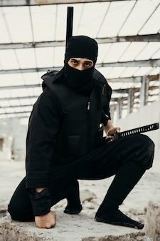 Schauspieler, der eine ninja-kriegerrolle in maske und outfits ausführt