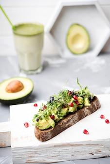 Scheibe brot mit avocado-nudeln und einem glas smoothie