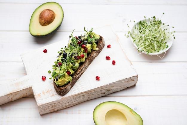Scheibe brot mit hoher ansicht der avocadoteigwaren und des granatapfels
