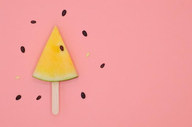 Scheibe der gelben wassermelone auf hölzernem stock der eiscreme mit samen für sommerzeit.