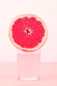 Scheibe der pampelmuse über dem glas gegen rosa hintergrund