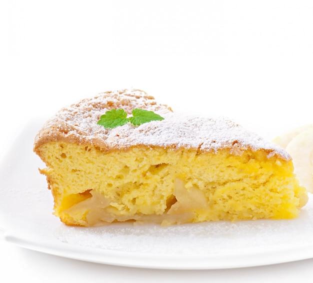 Scheibe des apfelfruchtkuchens auf einer platte verziert mit tadellosem blatt