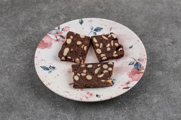 Scheibe des frischen kuchens drei auf platte. schokoladenkuchen mit erdnuss, hausgemacht.