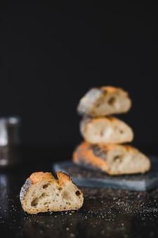 Scheibe des gebackenen brotes mit chia samen auf schwarzem hintergrund