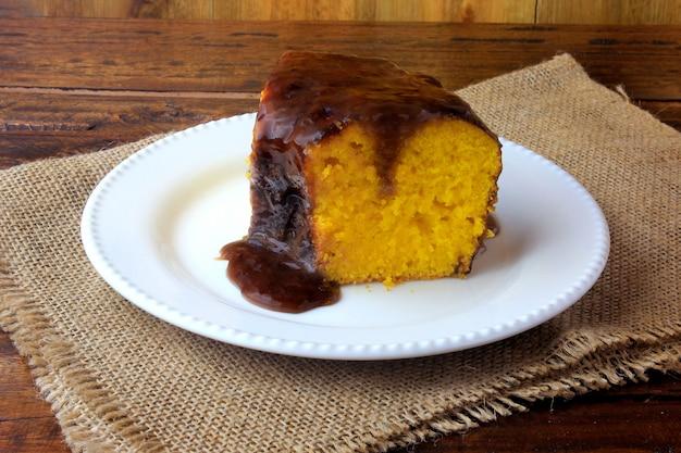 Scheibe des karottenkuchens mit schokoladenüberzug auf weißer keramischer platte
