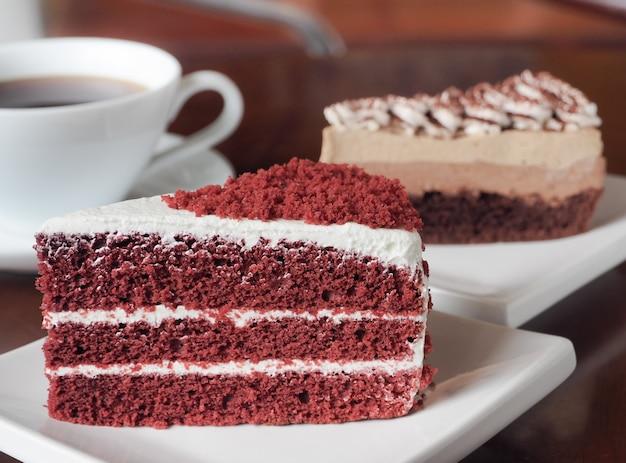 Scheibe des roten samtkuchens auf einer weißen platte. schließen sie oben vom roten samtschokoladenkuchen und vom tiramisukaffeekuchen mit einer schale heißem kaffee auf tabelle.