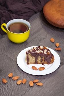 Scheibe des selbst gemachten bananenbrotes mit schokolade, mandel und gelber tasse tee auf holz