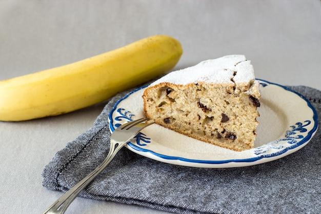 Scheibe des selbst gemachten bananenkuchens oder -brotes auf aufwändiger platte mit organischer gelber banane