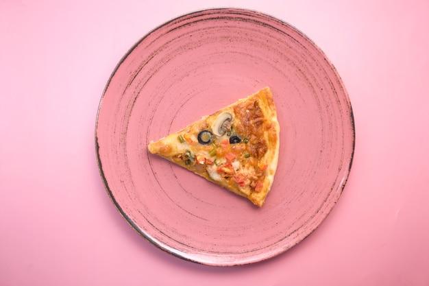 Scheibe gemüsepizza auf einem teller auf rosa tisch.