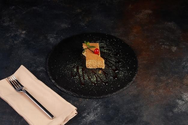 Scheibe geschichteten honigkuchens, dunkler hintergrund