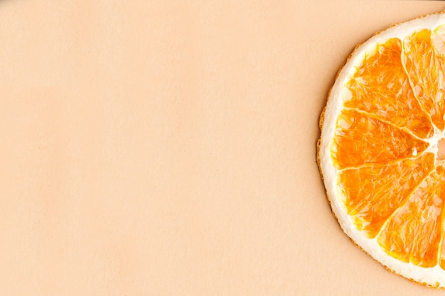 Scheibe getrocknete orange auf hellbraunem hintergrund mit platz für text. minimalismus, lebensmittelkonzept.