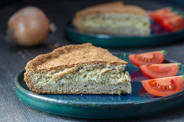 Scheibe hausgemachte zwiebel-quiche eine gebackene sahne-ei-torte mit käse und grünen kräutern, nahaufnahme