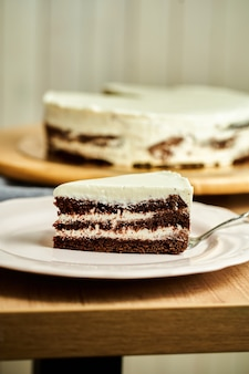 Scheibe hausgemachten schokoladenkuchen auf teller. holzhintergrund