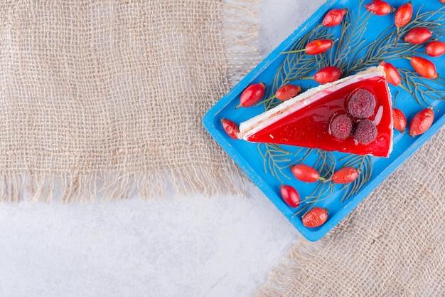 Scheibe käsekuchen mit frischen hagebutten auf blauem teller.