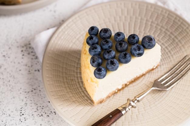 Scheibe klassischen new- yorkkäsekuchens mit blaubeeren auf weißer platte. nahaufnahme. hausbäckerei
