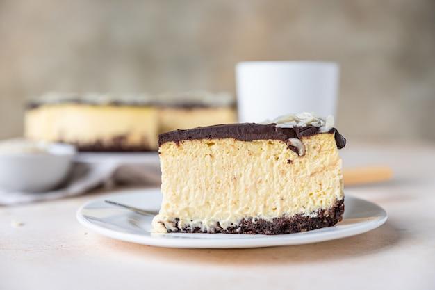 Scheibe ohne gebackenen cremigen käsekuchen mit schokoladenglasur und mandeln, heller betonhintergrund.
