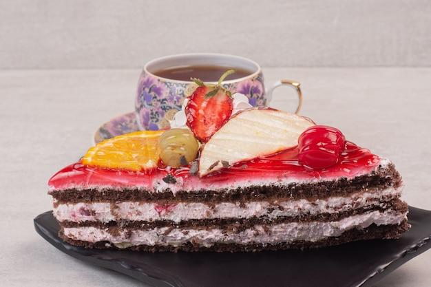 Scheibe schokoladenkuchen auf teller mit fruchtscheiben und tasse tee.