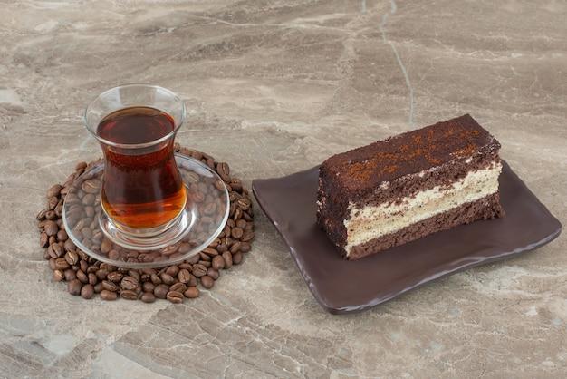 Scheibe schokoladenkuchen, kaffeebohnen und glas tee auf marmortisch.