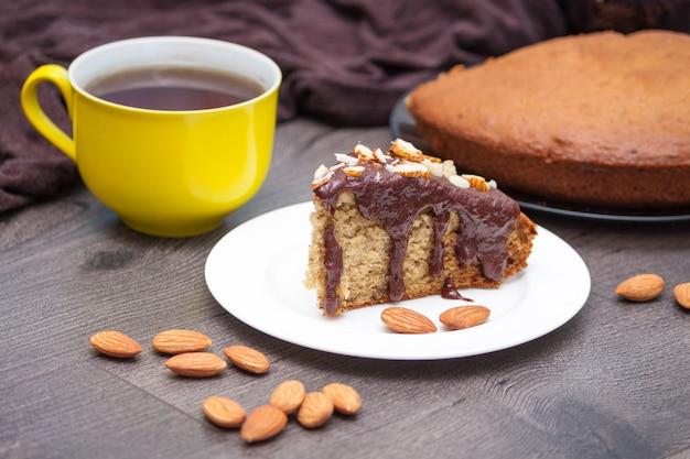 Scheibe selbst gemachtes bananenbrot mit schokolade, mandel und gelber tasse tee oder kaffee auf holz
