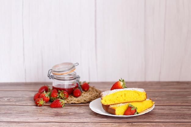 Scheibe shaker lemon pie auf weißem teller mit erdbeeren