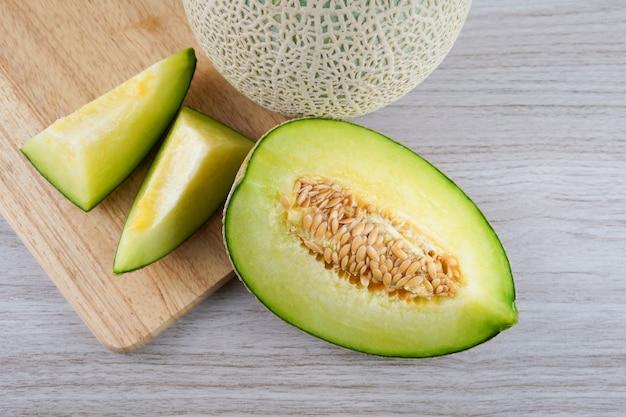 Scheibe von japanischen melonen, von honigmelone oder von kantalupe lokalisiert auf hölzernem. obst und ergänzungsmittel für eine gute gesundheit